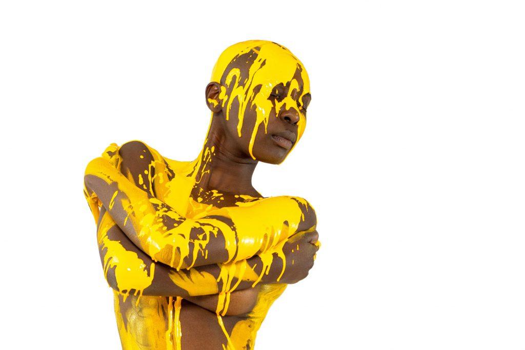 BODYART-Künstler Jörg Düsterwald hat Fotomodel Lenny sehr reduziert mit Farbe bemalt und anschließend mit gelber Farbe übergossen. Die Fotos während der Kunstperformance fertigte Fotograf Dennis Largo Schulz am 15.April 2019 in Hameln.
