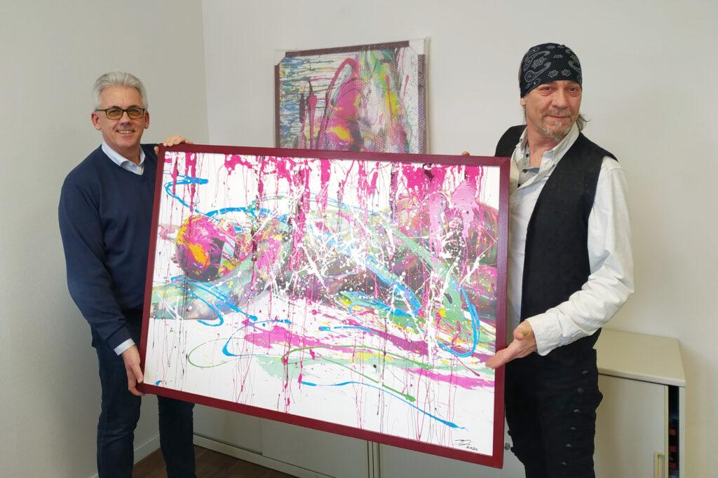 Künstler Jörg Düsterwald übergibt Armin Ahrens die beiden Gemälde PRINT.SPLASH-I und -II, die aus der ART-Performance in der Druckerei QUBUS.media GmbH im Sommer 2020 resultieren. Das Unternehmen aus Hannover hat die beiden Werke käuflich erworben. Hannover, 15. Februar 2021