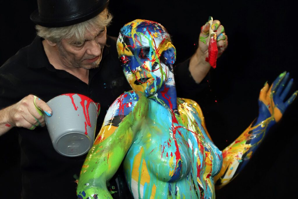 Künstler Jörg Düsterwald führt im Kunstkreis Hameln eine Bodyart Performance live vor Publikum vor. Das nackte Fotomodell wird dabei mit flüssiger Farbe übergossen